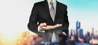 Businessman with hand in holding something position, with panoramic city view in sunrise background Stock Photos