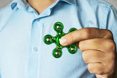 Businessman hand holding spinner and showing tricks. Relieving stress, popular fidget spinner. Antistress toy Stock Photos