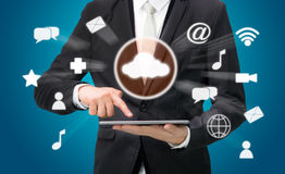 Businessman hand holding tablet cloud connectivity. On blue background Royalty Free Stock Images