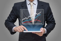 Businessman hand holding tablet graph finance on gray background Royalty Free Stock Images
