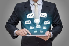 Businessman hand holding tablet messages. Or letter on gray background Royalty Free Stock Photos