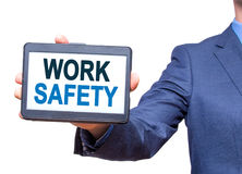Businessman hand holding tablet with WORK SAFETY text sign. Isolated on white. Business concept. Stock photo royalty free stock photo