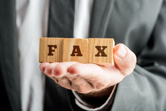 Businessman hand holding three wooden cubes reading FAX Stock Photography