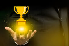 Businessman hand holding trophy.financial,success Royalty Free Stock Photography