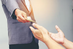 Businessman hand holding US dollar, USD. bills, offers dollar bank note money and giving money Paid for Something by Cash in Busin Stock Image