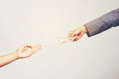 Businessman hand holding US dollar, USD. bills, offers dollar bank note money and giving money Paid for Something by Cash in Busin Royalty Free Stock Images