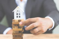 Businessman hand holding wood block with model white house. Investment risk and uncertainty in the real estate housing market. stock images