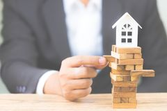Businessman hand holding wood block with model white house. Investment risk and uncertainty in the real estate housing market. stock photo