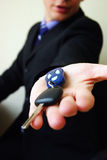 Businessman hand with keys. A businessman offering a bunch of car keys and car alarm system Stock Image