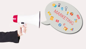 Businessman hand with loudspeaker with symbols flying out. Marketing Stock Photos