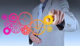 Businessman hand makes colorful gear to success Royalty Free Stock Images