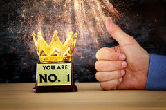 Businessman hand next to award trophy for show victory or winning first place Royalty Free Stock Photos