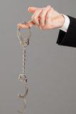 Businessman hand with opened handcuffs Stock Photos