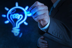 Businessman hand with a pen drawing light bulb Stock Photos