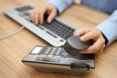 Businessman hand picking up telephone receiver on business workp Royalty Free Stock Photo