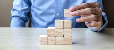 Businessman hand placing or pulling wooden block on the building. Business planning, Risk Management, Solution and strategy royalty free stock images