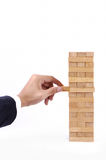 Businessman Hand playing with the wood game (jenga). Royalty Free Stock Photo