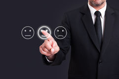 Businessman hand pointing the smiley face icon from screen Stock Images