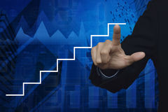 Businessman hand pointing stair symbol over graph and city tower Royalty Free Stock Photography