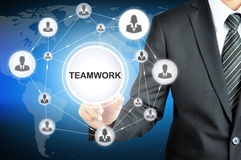 Businessman hand pointing on TEAMWORK sign on virtual screen. With human icons linked as network Royalty Free Stock Photo