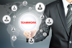 Businessman hand pointing on TEAMWORK sign on virtual screen. With human icons linked as network Royalty Free Stock Photos