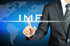 Businessman hand pointing to IMF (International Monetary Fund) sign. On virtual sceen Royalty Free Stock Images