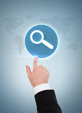 Businessman hand pointing to magnifying glass Royalty Free Stock Photos