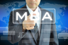 Businessman hand pointing to MBA sign on virtual screen Stock Photo