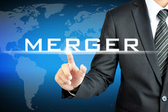 Businessman hand pointing to MERGER sign. On virtual screen Stock Image