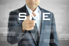 Businessman hand pointing to SME sign on virtual screen Royalty Free Stock Photo