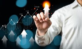 Businessman hand pointing up arrow with growing stock market financial planning.