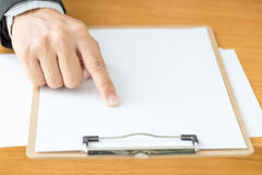 Businessman hand pointing white paper on wood desk Stock Photos