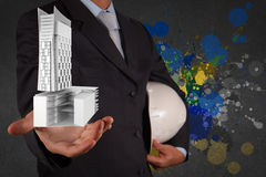 Businessman hand presents building development Stock Photos