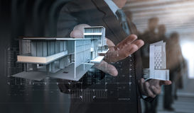 Businessman hand presents house model on modern computer Stock Photos