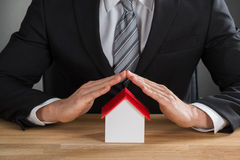 Businessman Hand Protecting House Model Stock Images