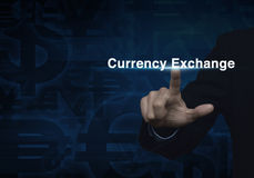 Businessman hand pushing currency exchange word on dark blue cur Royalty Free Stock Photography