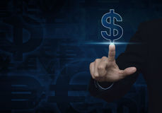 Businessman hand pushing dollar currency icon on dark blue backg Royalty Free Stock Image