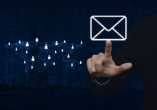 Businessman hand pushing email icon with light blue world map co Stock Images