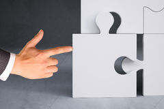 Businessman hand pushing puzzle piece Stock Photography