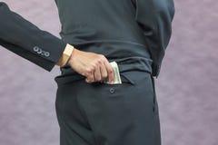 Businessman hand put money to back pocket Royalty Free Stock Photos