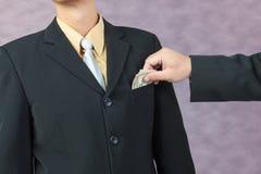 Businessman hand put money to pocket Royalty Free Stock Photos