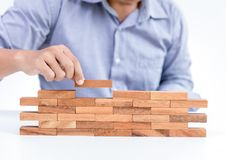 Businessman hand put wooden toy block stock photo
