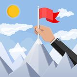 Businessman hand puts flag on peak of mountain. Business success, target, triumph, goal or achievement. Winning of competition. Rocky mountains, sky with Royalty Free Stock Image