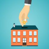 Businessman hand putting coin inside the house. Stock Images