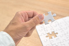 Businessman hand putting a missing piece into jigsaw puzzle Royalty Free Stock Photo