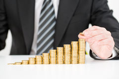 Businessman hand putting money coin stack growing business. Royalty Free Stock Photo
