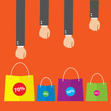Businessman hand reaches for the paper shopping bags standing Royalty Free Stock Photography