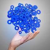 Businessman hand showing blue gears cogs royalty free stock photo