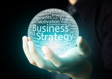 Businessman hand showing business strategy word. In crystal ball