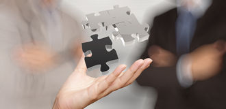 Businessman hand showing 3d puzzle